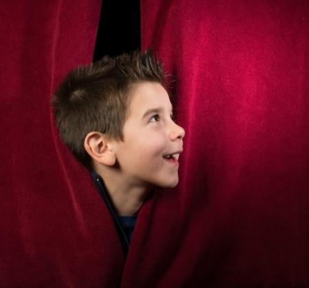 enfant derrière le rideau de théâtre